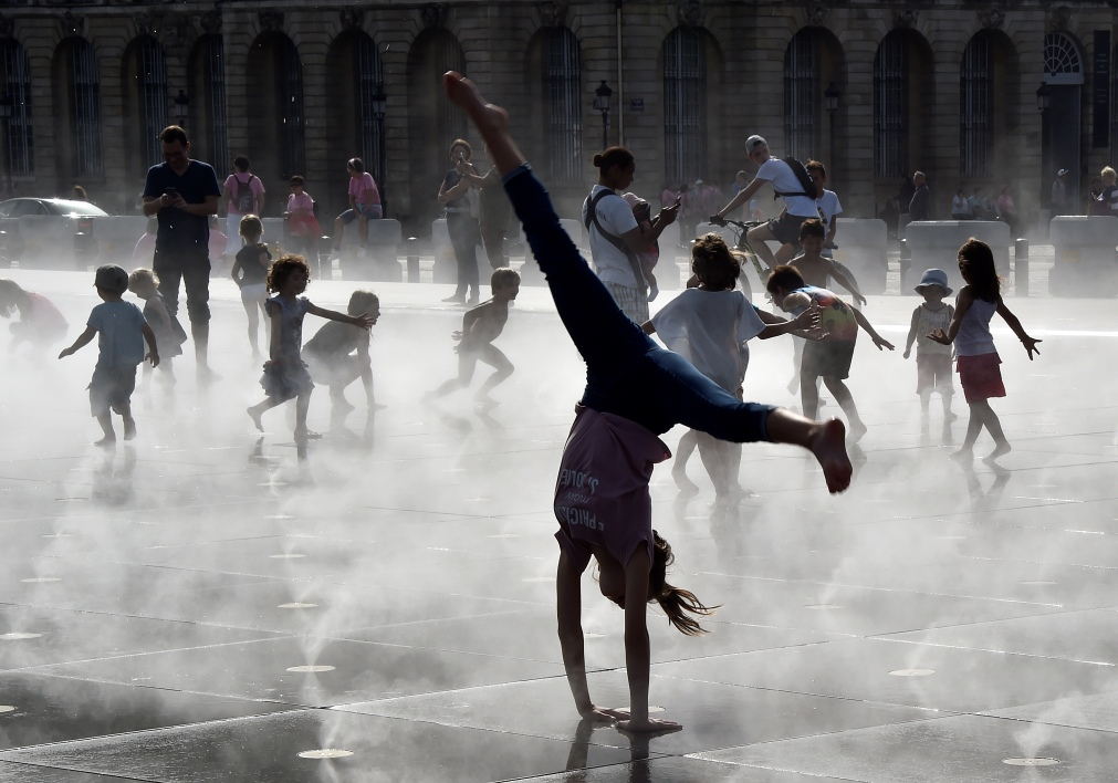 Children refresh themselves in the Miroir d'eau fountain in front of the Place de la Bourse during warm temperatures in Bordeaux, southwestern France, on October 15, 2017.  GEORGES GOBET / AFP