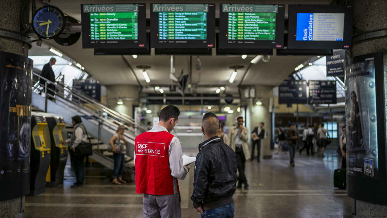 A SNCF employee helps a traveler at the Part-Dieu railway station, on June 11, 2014 in Lyon, on the first day of a national strike by French SNCF railway company employees. French commuters faced traffic chaos today amid a national train strike called by trade unions in protest against a proposed railway reform aimed at containing the sector's soaring debt. The 24-hour strike began on Tuesday evening, but its main impact will be felt on Wednesday with train links to other countries also hit, according to the SNCF state rail body. AFP PHOTO / JEFF PACHOUDA SNCF employee helps a traveler at the Part-Dieu railway station, on June 11, 2014 in Lyon, on the first day of a national strike by French SNCF railway company employees. French commuters faced traffic chaos today amid a national train strike called by trade unions in protest against a proposed railway reform aimed at containing the sector's soaring debt. The 24-hour strike began on Tuesday evening, but its main impact will be felt on Wednesday with train links to other countries also hit, according to the SNCF state rail body. AFP PHOTO / JEFF PACHOUD