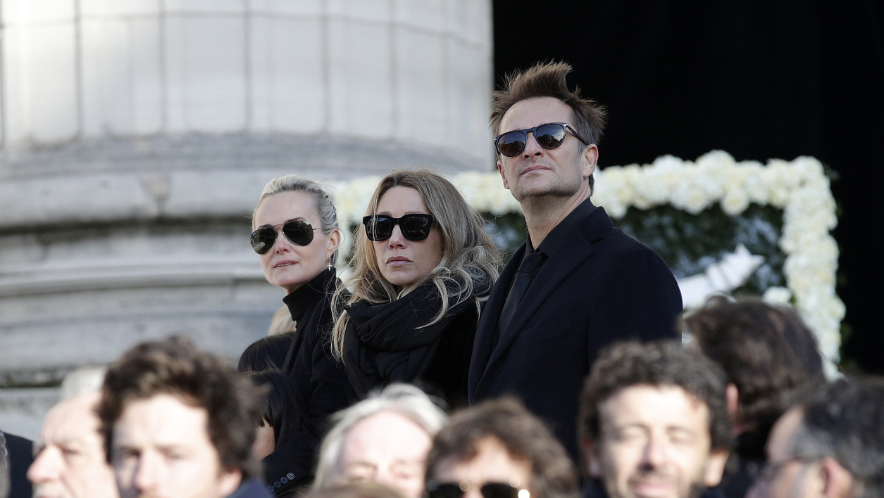 In this file photo taken on December 9, 2017 Laeticia Hallyday, (L), wife of late French singer Johnny Hallyday, his son David Hallyday and daughter Laura Smet (C) stand during his funeral ceremony outside the Eglise de la Madeleine (La Madeleine Church) in Paris.