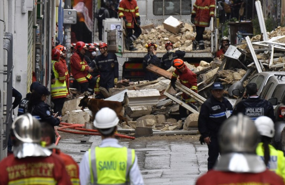 People are at work at the start of the clearance work at the site where two buildings collapsed, resulting in at least two people injured, on November 5, 2018 in Marseille.  GERARD JULIEN / AFP