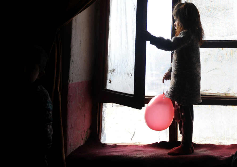 AFGHANISTAN, Mazar-i-Sharif : Afghan girl Fereshta holds a balloon as she looks out of a window of her house in Mazar-i-Sharif on February 15, 2014. The year 2013 was the worst year for Afghan women and children casaulties with an increase of 34% in the number of children killed or wounded due to fighting between Taliban and Afghan security forces, according to the United Nations Assistance Mission for Afghanistan (UNAMA). AFP PHOTO/ Farshad USYAN