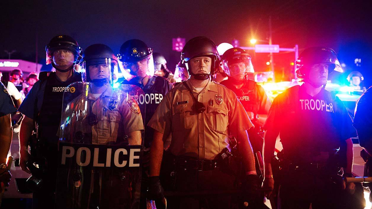 St. Louis County Police and Missouri State Highway Patrol troopers stand guard as protesters march on West Florissant Avenue in Ferguson, Missouri on August 9, 2015. A day of peaceful remembrance marking the anniversary of 18-year-old black teen Michael Brown's killing by police in the US city of Ferguson came to a violent end on August 9 as gunfire left at least one protester injured. AFP PHOTO / MICHAEL B. THOMAS