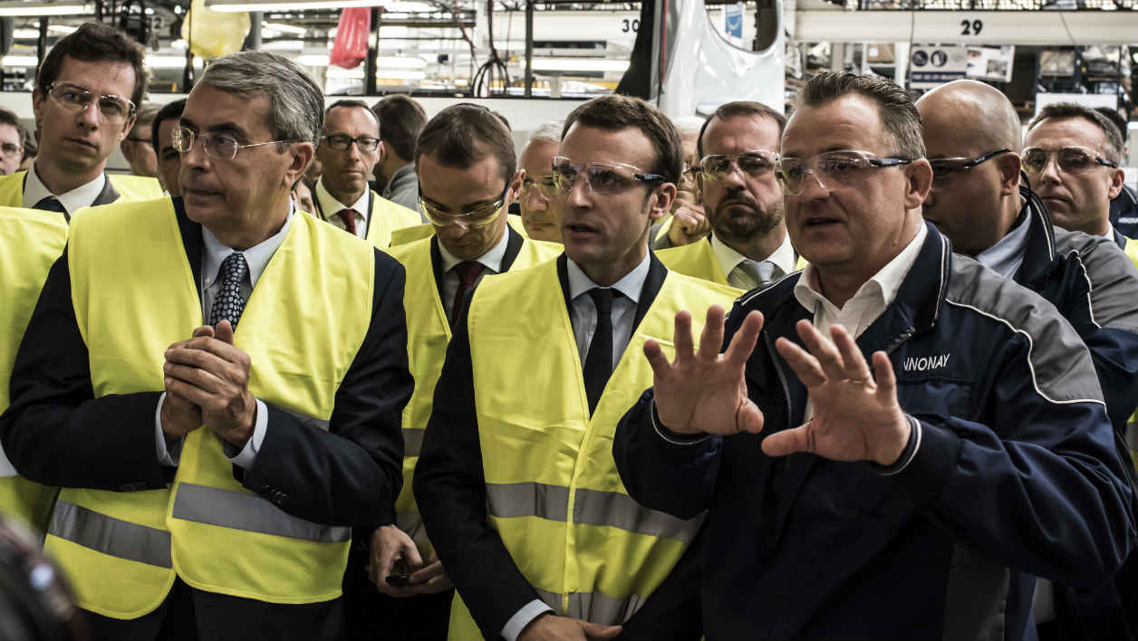 French Economy Minister Emmanuel Macron (C) visits the plant of bus manufacturer Iveco in Annonay, a subsidiary of the US-Italian company CHN industrial (ex-Fiat industrial), the last bus production site and one of the brand's most important plants in Europe. AFP PHOTO / JEAN-PHILIPPE KSIAZEK