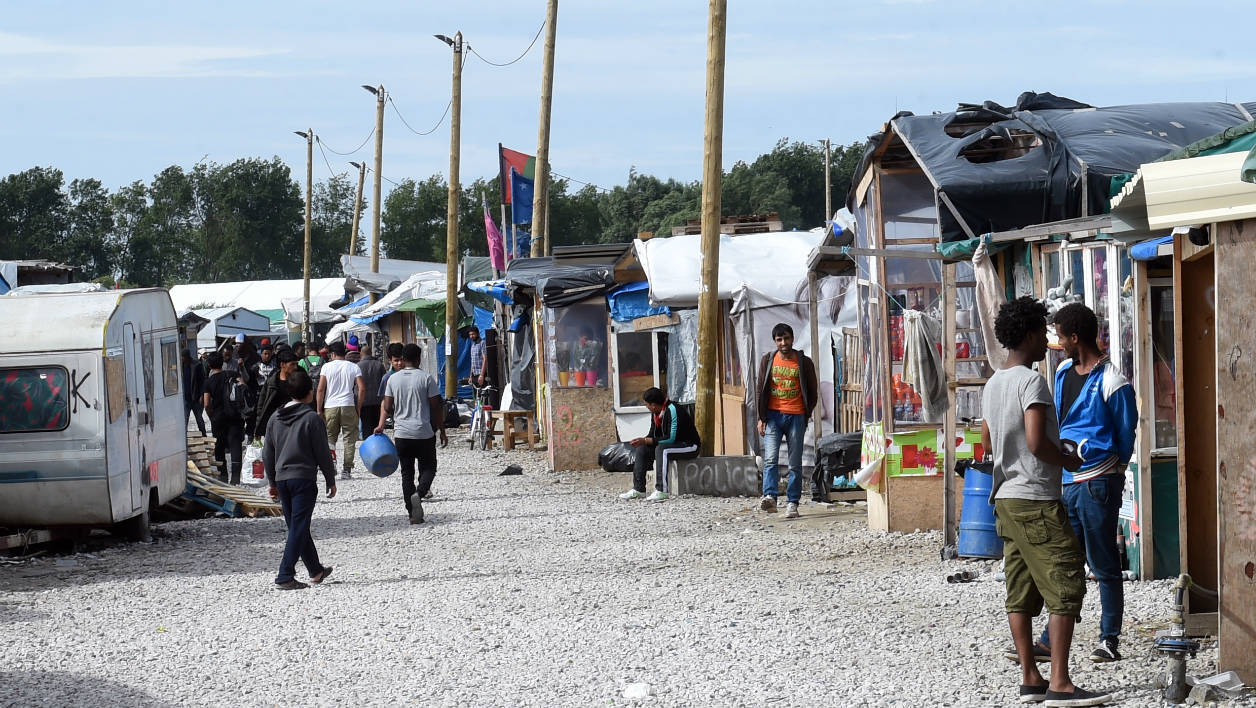 "People walk in the ""Jungle"" migrant camp in Calais on July 15, 2016. French authorities began dismantling the ""Jungle"" in March, but several thousand migrants refused to move out and remain holed up there, hoping to find a way to Britain. FRANCOIS LO PRESTI / AFP"