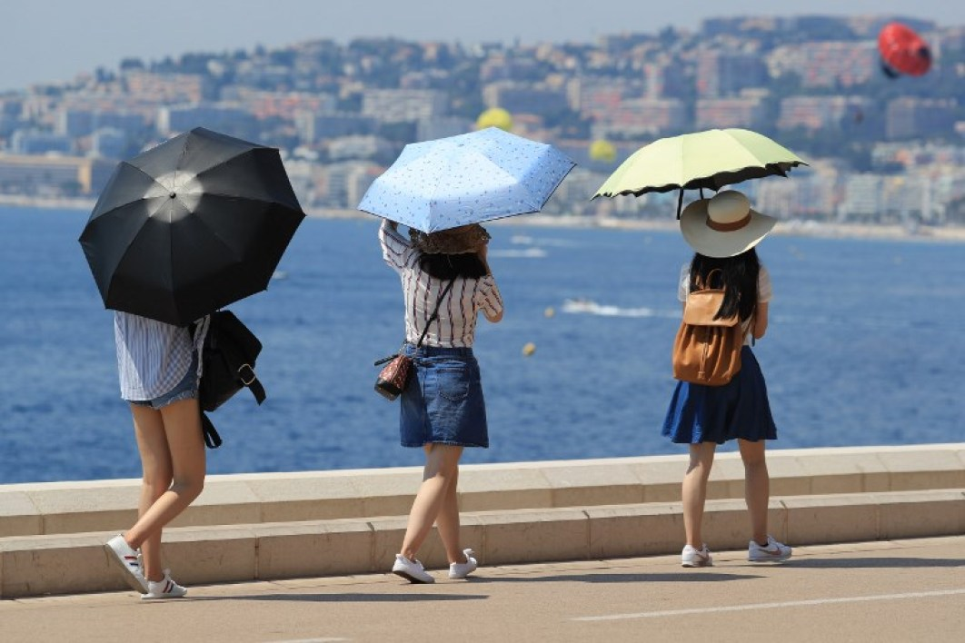 People shelter from the sun under umbrellas as they look out over the Meditteranean Sea at Nice, south-eastern France on August 3, 2018, as heatwave conditions prevail over Europe.  VALERY HACHE / AFP