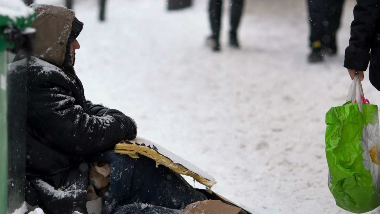 homeless person sits in a snow covered street in Paris on January 20, 2013 following snow falls over the French capital overnight. - JOEL SAGET / AFP
