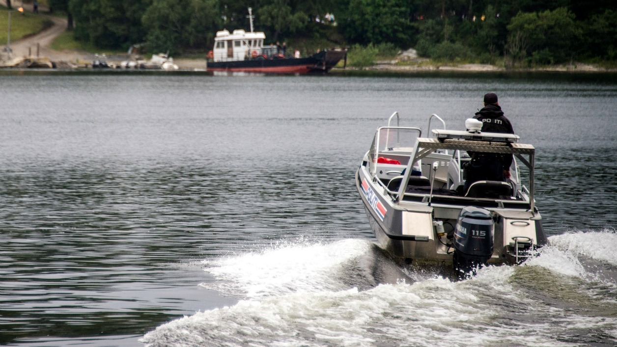 A police officer drives a boat on his way to the Utoya island some 40 km west of Oslo on August 7, 2015 where the Norwegian Labour Party Youth division ( AUF ) holds their first summer camp session since the 2011 bloodbath.On July 22, 2011 far-right extremist Anders Behring Breivik massacred 69 people during an AUF camp on the island.