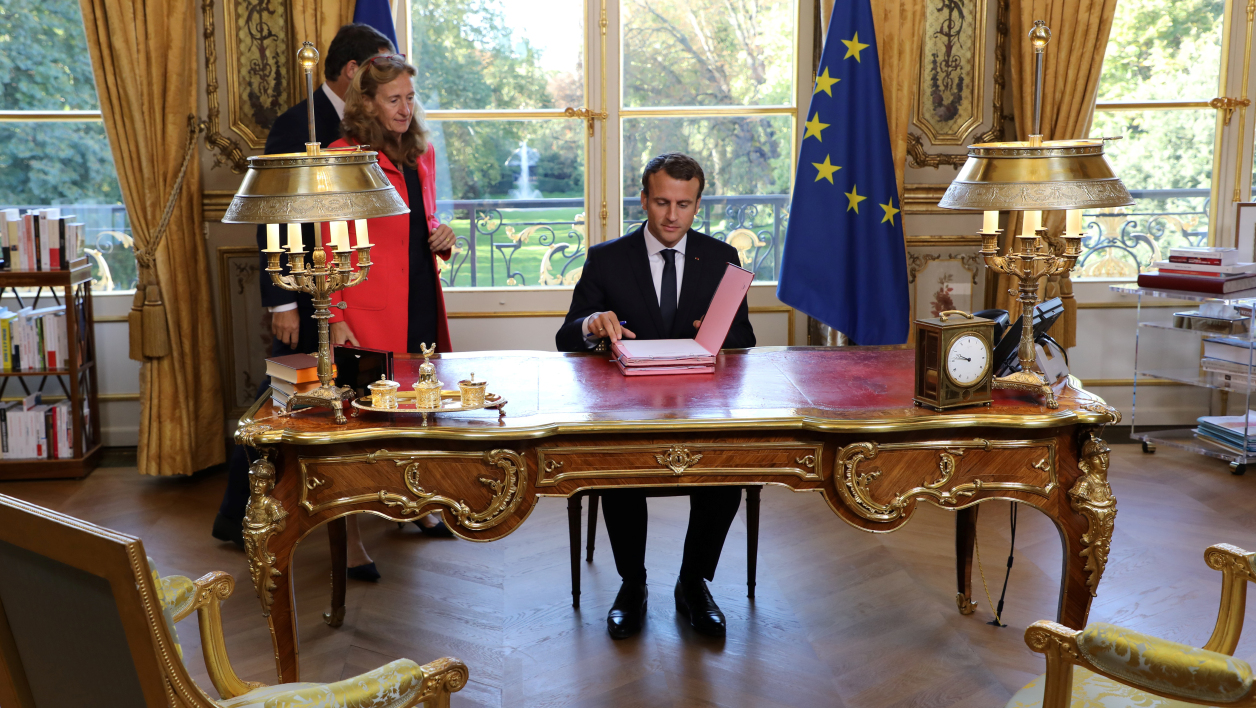 French President Emmanuel Macron (C), flanked by Justice Minister Nicole Belloubet and Junior Minister for the Relations with Parliament and Government Spokesperson Christophe Castaner, arrives to sign documents to promulgate the bills for faith in French political life on September 15, 2017 in his office at the Elysee Palace in Paris.  LUDOVIC MARIN / AFP