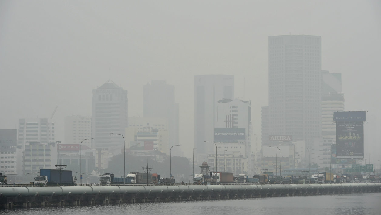 """Lorries travelling across the causeway from haze-choked Malaysia's southern state of Johor (background) are seen driving towards Singapore on September 30, 2015. Singapore's Pollutant Standards Index, which measures air quality, climbed to """"unhealthy"""" levels September 30 as Malaysia, Singapore and large expanses of Indonesia have suffered for weeks from acrid smoke billowing from fires on plantations and peatlands that are being illegally cleared by burning. AFP PHOTO / ROSLAN RAHMAN"""