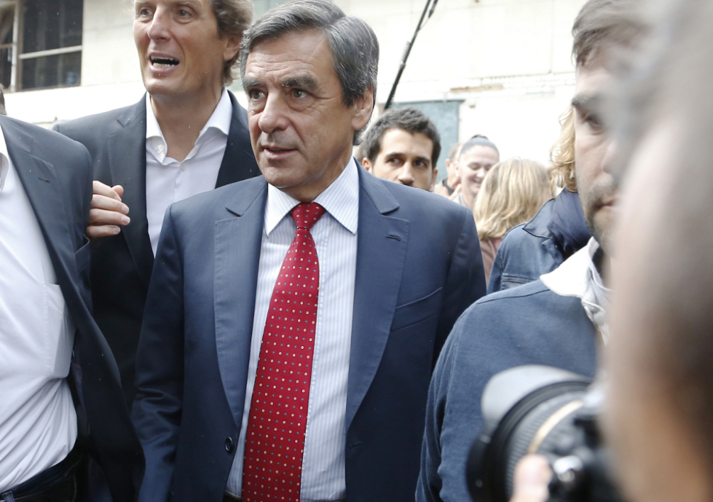 FRANCE, Piscop : French former prime minister and member of a triumvirate leading the French right-wing UMP party, Francois Fillon (C) flanked by party member and mayor of Domont Jerome Chartier (3rdL) arrives for a barbecue with right-wing party UMP militants on September 21, 2014 in Piscop, near Domont, a suburb of Paris. AFP PHOTO / THOMAS SAMSON