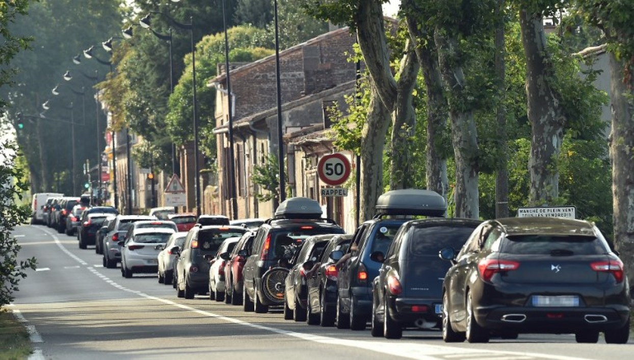 "Traffic stands at a halt in the village of Villenouvelle between Villefranche de Lauragais and Toulouse on August 4, 2018, on the first major weekend of the French summer holidays. This weekend is expected to be ""most difficult of the summer"" for traffic, with hundreds of kilometers of traffic jams, as holiday-makers start or end their holidays. REMY GABALDA / AFP"