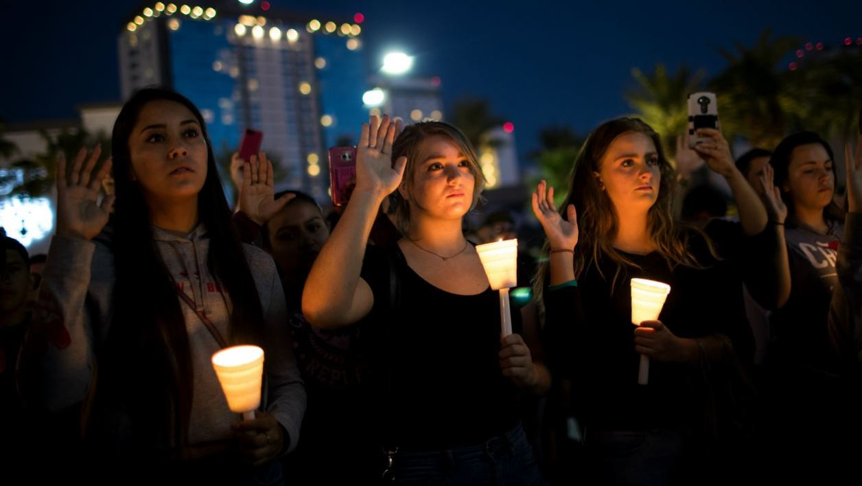 LAS VEGAS, NV - OCTOBER 2: Mourners hold up their right hand as they pledge to spread peace and love as they attend a candlelight vigil at the corner of Sahara Avenue and Las Vegas Boulevard for the victims of Sunday night's mass shooting, October 2, 2017 in Las Vegas, Nevada.