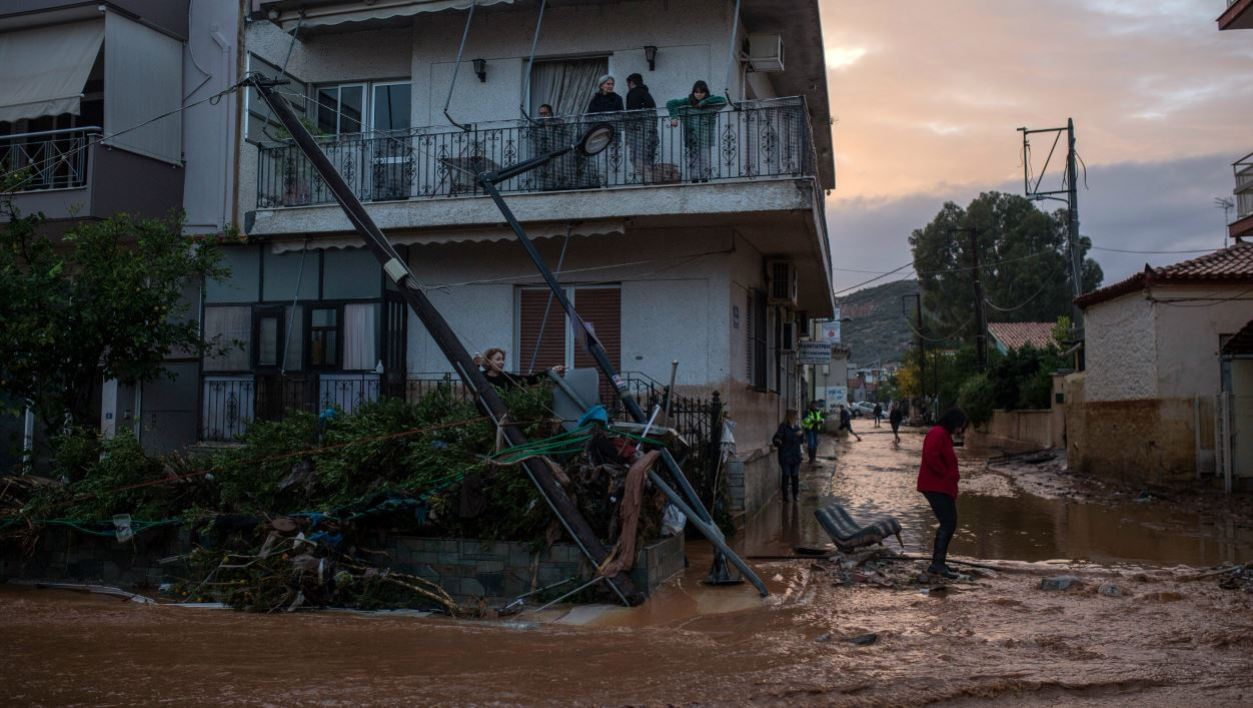 A person walks past debris and a downed power line in a flooded street in the town of Mandra, northwest of Athens, on November 15, 2017, after heavy overnight rainfall in the area caused damage and left seven people dead. At least seven people died on November 15 and more were missing after a strong overnight downpour flooded three towns in Greece, officials said.