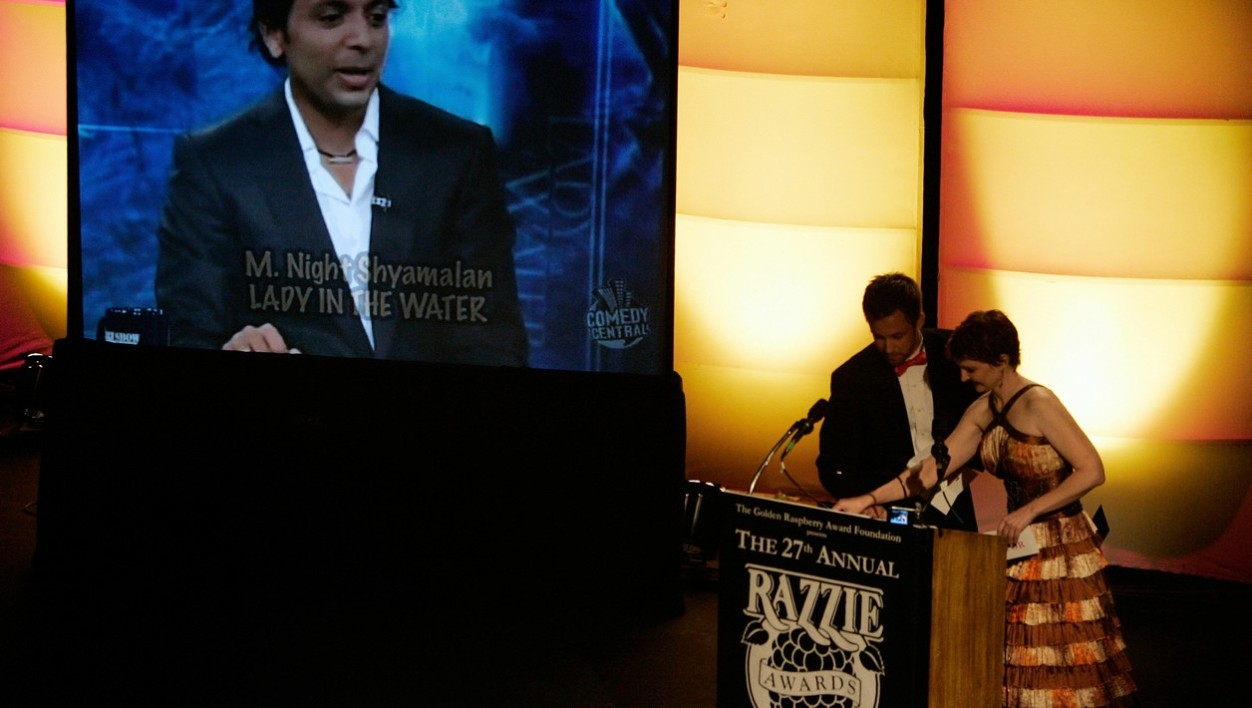 "A clip of the winner for ""Worst Director"", Night Shyamalan for his movie ""Lady in the Water"" is displayed next to presenters Rebecca Marcotte and Aaron Sawyer during the Razzie Awards in Hollywood, CA, 24 February 2007. The ""Razzie"" a gold-spray-painted, golf-ball-size raspberry atop of a mangled super 8 film reel trophy, with an estimated street value of 4.97 dollars, awards the worst movie and actors"