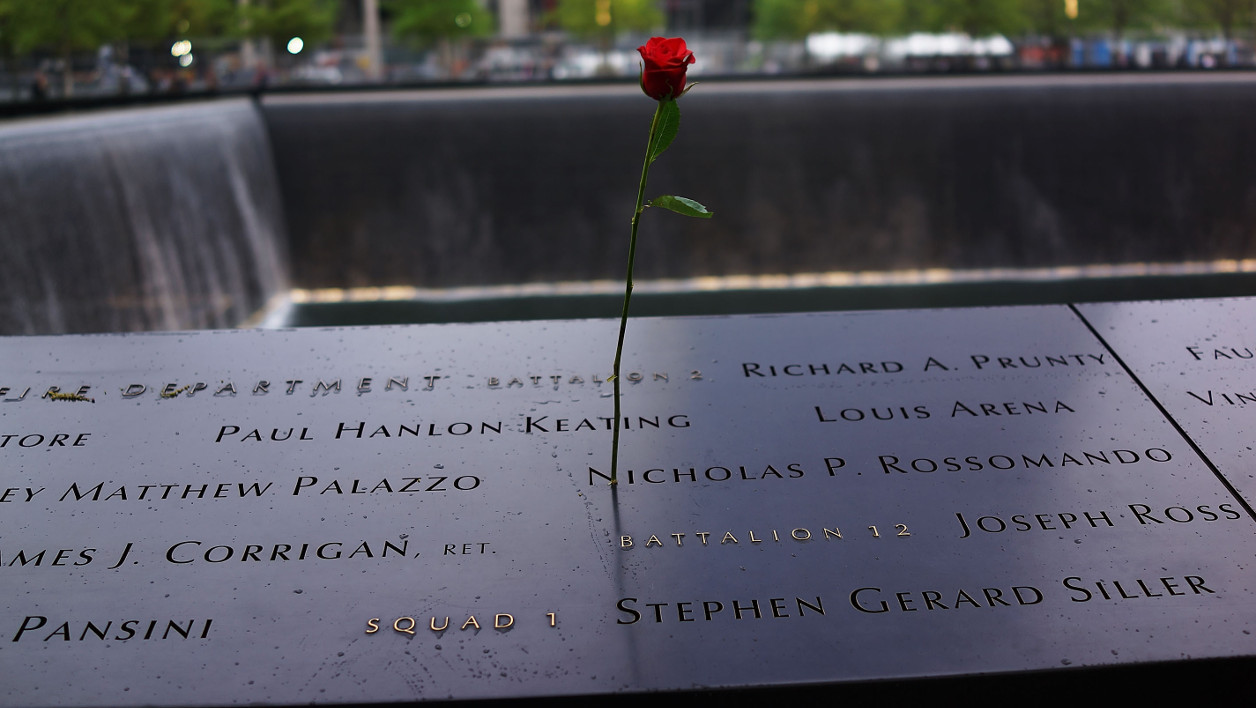 A rose is placed on a name engraved along the South reflecting pool at the Ground Zero memorial site during the dedication ceremony of the National September 11 Memorial Museum in New York on May 15, 2014. The museum will open to the public on May 21. AFP PHOTO/POOL/ Spencer Platt SPENCER PLATT / POOL / AFP