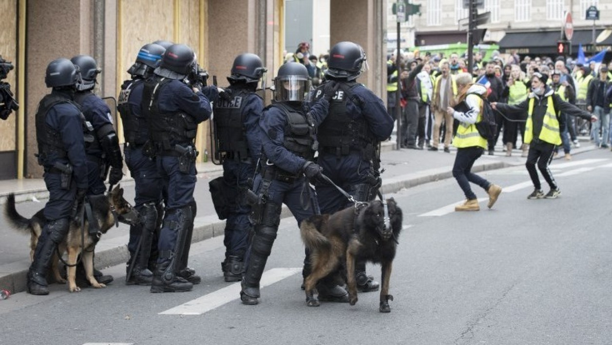 """French riot police officers with dogs face """"Yellow vests"""" (gilets jaunes) protestors near the Arc de Triomphe in Paris on December 8, 2018 during a protest against rising costs of living they blame on high taxes. Paris was on high alert on December 8 with major security measures in place ahead of fresh """"yellow vest"""" protests which authorities fear could turn violent for a second weekend in a row. Thomas SAMSON / AFP"""