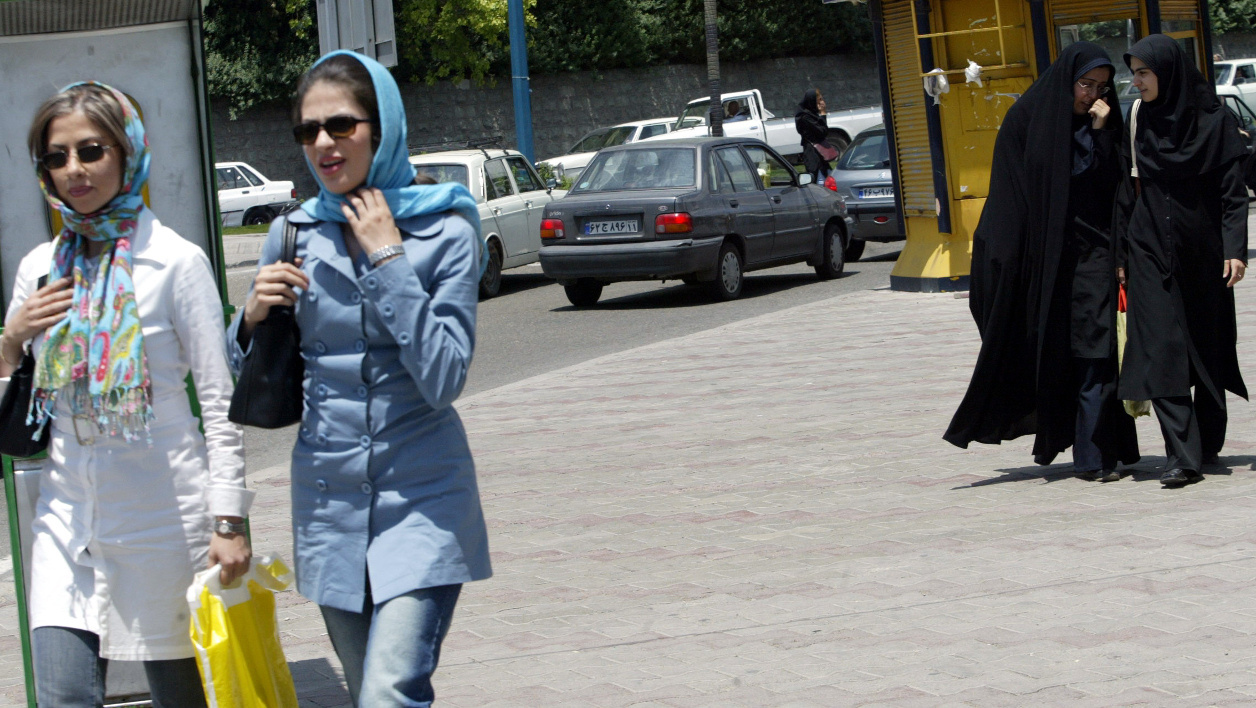 "Iranian women walk in different western and traditional costumes northwest of Tehran, 02 June 2005. For the past 26 years, Iran's ruling clerics have been at pains to keep women under wraps and away from the risk of ""Westoxication"". Iranian women may be obliged to wear the chador -- literally meaning tent -- or otherwise a long coat and headscarf whenever they head outdoors, but that has not dampened their appetite to pamper themselves. AFP PHOTO/BEHROUZ MEHRI BEHROUZ MEHRI / AFP"