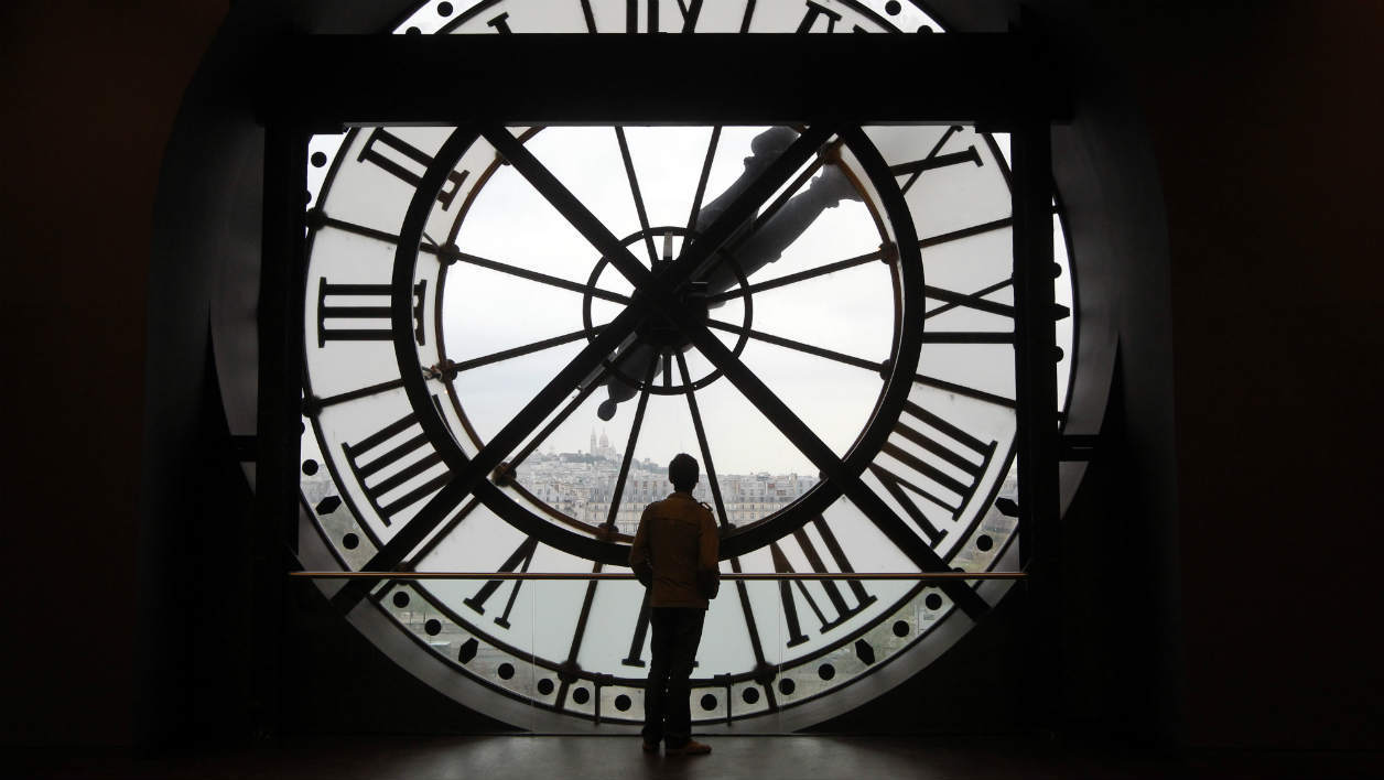 A man looks at the Seine river through the giant clock of the Orsay Museum in Paris, on October 12, 2011. With the inauguration, today, of new galleries, the museum, created 25 years ago, gains some 2,000m2 new space. AFP PHOTO PIERRE VERDY