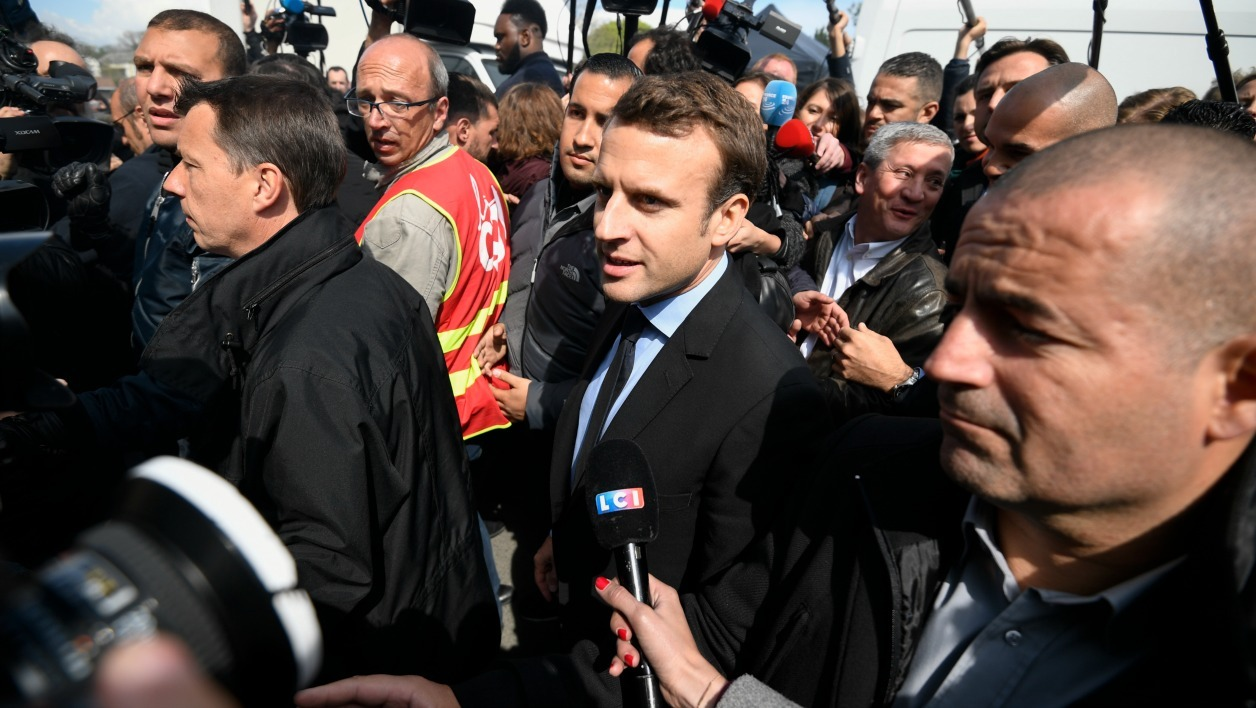 French presidential election candidate for the En Marche ! movement Emmanuel Macron (C) speaks to journalists as he arrives at the Whirlpool factory on April 26, 2017, in Amiens. French presidential frontrunner Emmanuel Macron was met on April 26, 2017 with boos and chants in favour of his far-right rival as he made a chaotic visit to an under-threat factory in northern France.