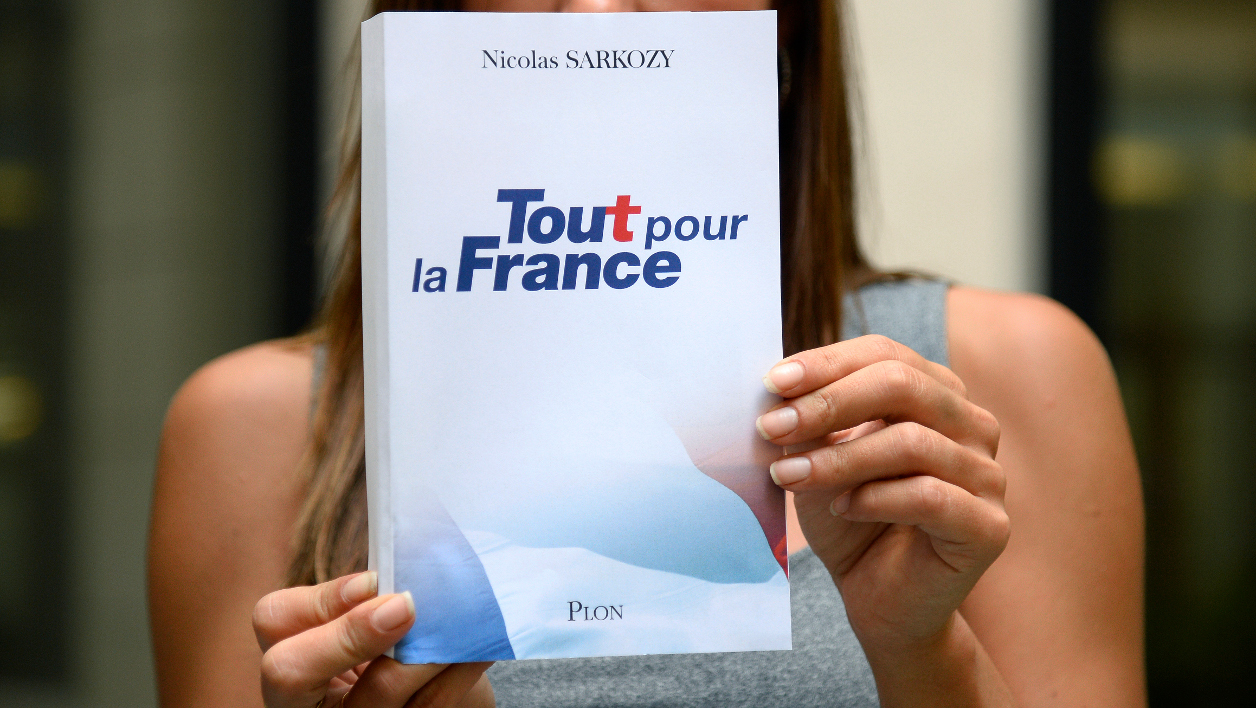 """A woman holds up a copy of the upcoming book penned by France's right-wing Les Republicains (LR) party president Nicolas Sarkozy, where he announces officially his candidacy to the 2017 French Presidential Elections, in Paris on August 22, 2016. """"I have decided to be a candidate in the 2017 presidential election,"""" Sarkozy, who was president between 2007 and 2012, wrote in the foreword to a new book """"Tout pour la France"""" (All for France) due out later this week. BERTRAND GUAY / AFP"""