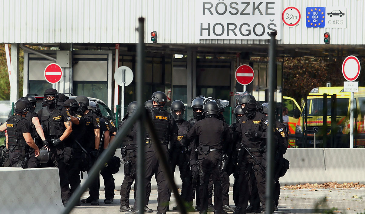 Hungarian riot police prepare for duty as migrants attempted to break out from the no-man's land between the two countries at the Hungarian-Serbian border of Roszke station on September 16, 2015. Hungarian police fired tear gas and water cannon at several hundred migrants protesting at being unable to cross the border from Serbia and throwing missiles, AFP reporters said.