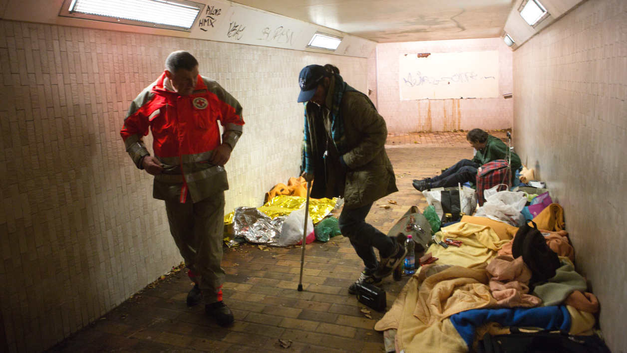 French Red Cross (Croix rouge) volunteers attend to a homeless person living in a train station tunnel, on November 3, 2012 in Chatou, outside Paris, during a night round of French social Samu (social emergency unit). AFP PHOTO LOIC VENANCE