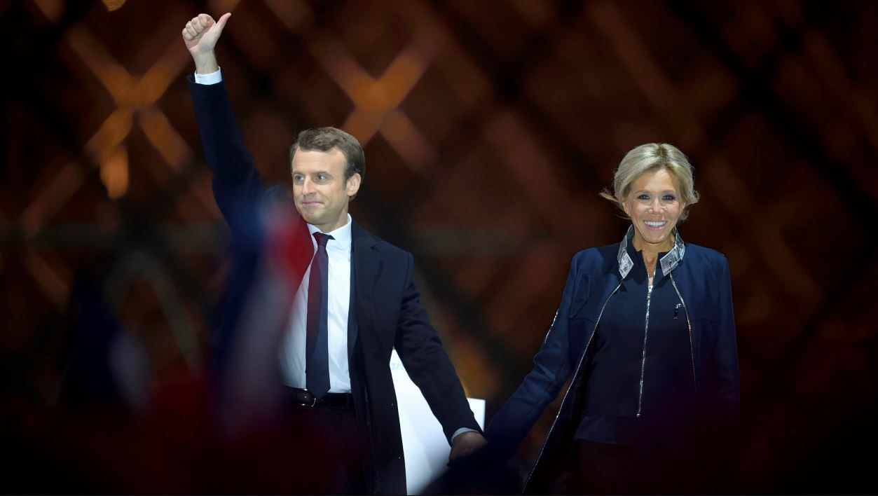French president-elect Emmanuel Macron (L) and his wife Brigitte Trogneux greet supporters in front of the Pyramid at the Louvre Museum in Paris on May 7, 2017, after the second round of the French presidential election. Emmanuel Macron was elected French president on May 7, 2017 in a resounding victory over far-right Front National (FN - National Front) rival after a deeply divisive campaign, initial estimates showed. Eric FEFERBERG / AFP