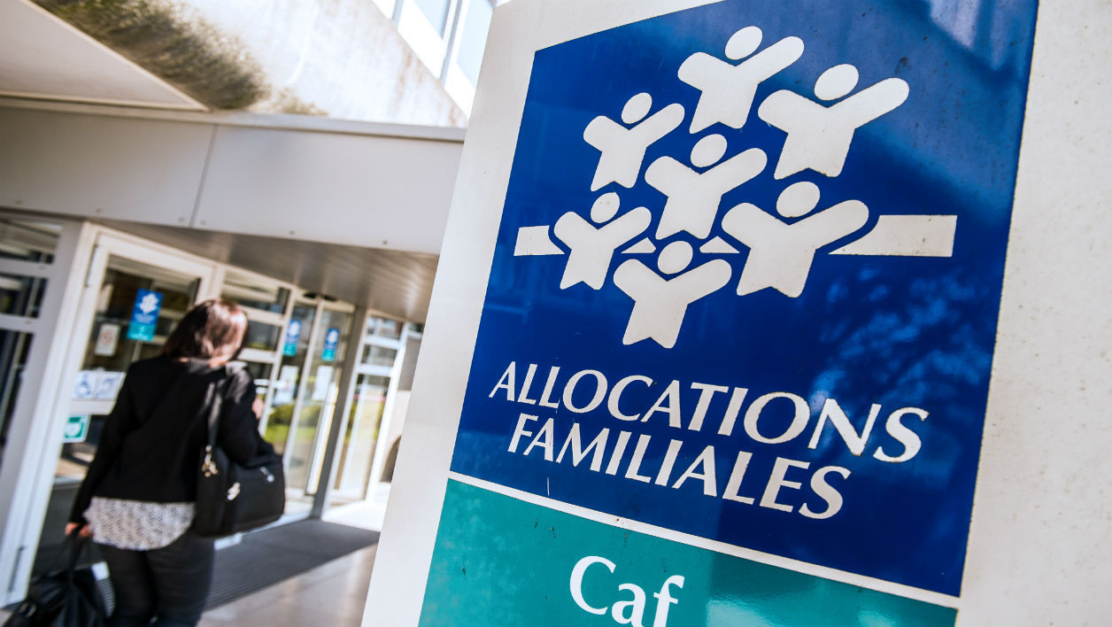 A woman walks past a branch of the Caisse d'Allocations Familiales (Family Allocations Office, or CAF) in Calais on April 15, 2015. AFP PHOTO PHILIPPE HUGUEN  PHILIPPE HUGUEN / AFP