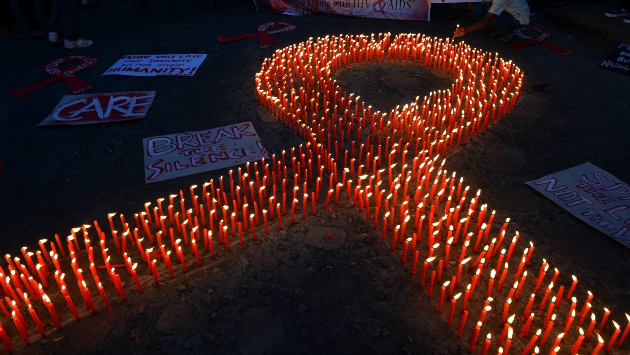 An AIDS activist lights a group of candles placed in the shape of a red ribbon during an event marking World AIDS Day in Manila on December 1, 2012. Discrimination against homosexuals and people infected with HIV is contributing to the rapid rise of the incurable disease in the Philippines, officials and health activists said. AFP PHOTO/TED ALJIBE TED ALJIBE / AFP