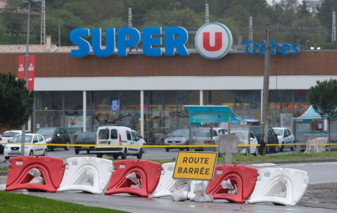 "This picture taken in the town of Trebes, southwestern France on March 24, 2018 shows a sign reading ""Closed road"" at the entrance of the Super U supermarket where a gunman took hostages in a string of attacks that left a total of four people dead, before being killed by security forces on March 23, 2018. Four people were killed on March 23 when a man claiming allegiance to the Islamic State group went on a shooting spree and held people hostage in a supermarket in southwest France before being shot dead by police."