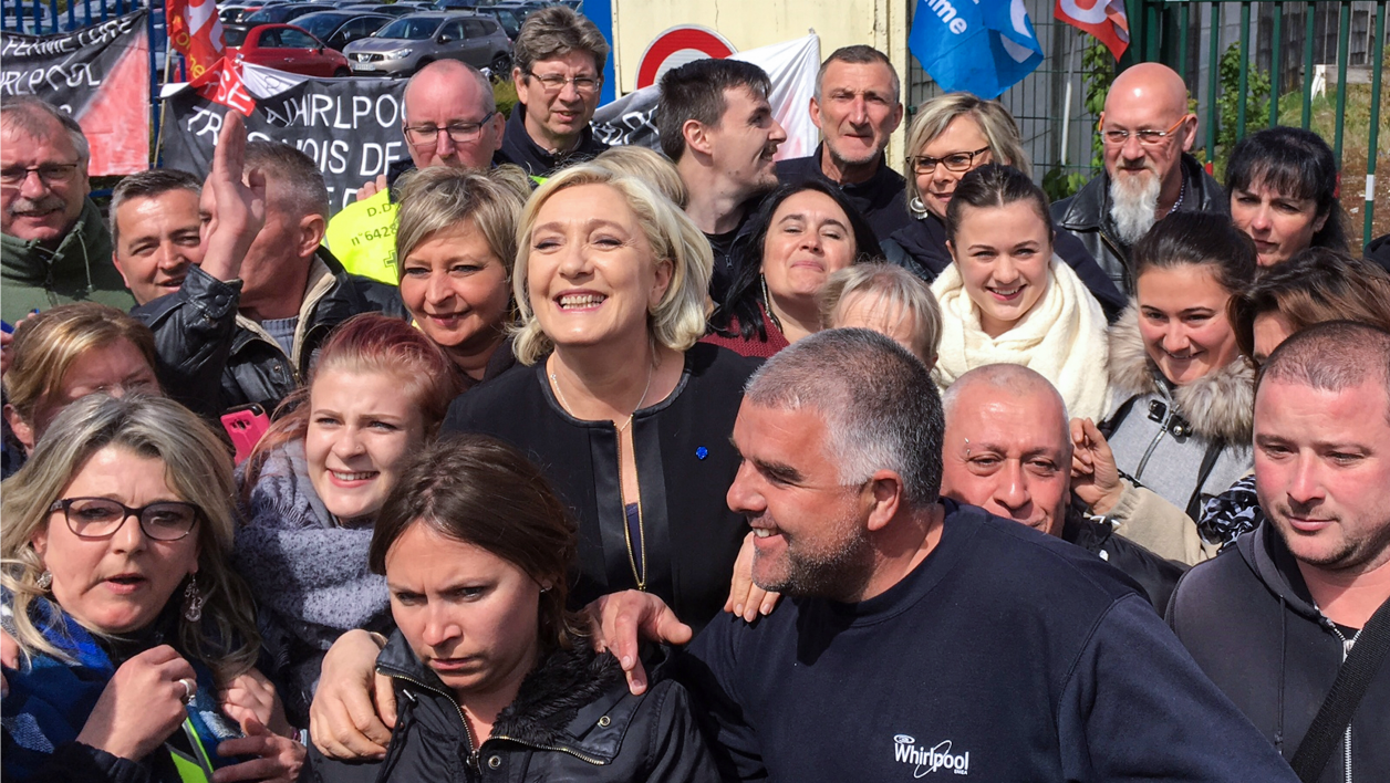 French presidential election candidate for the far-right Front National (FN) party, Marine Le Pen (C) smiles with people in front of the Whirlpool factory in Amiens, northern France, on April 26, 2017. French far-right presidential candidate Marine Le Pen upstaged her rival Emmanuel Macron by making a surprise visit to an under-threat factory just as he was visiting the town where it is based.