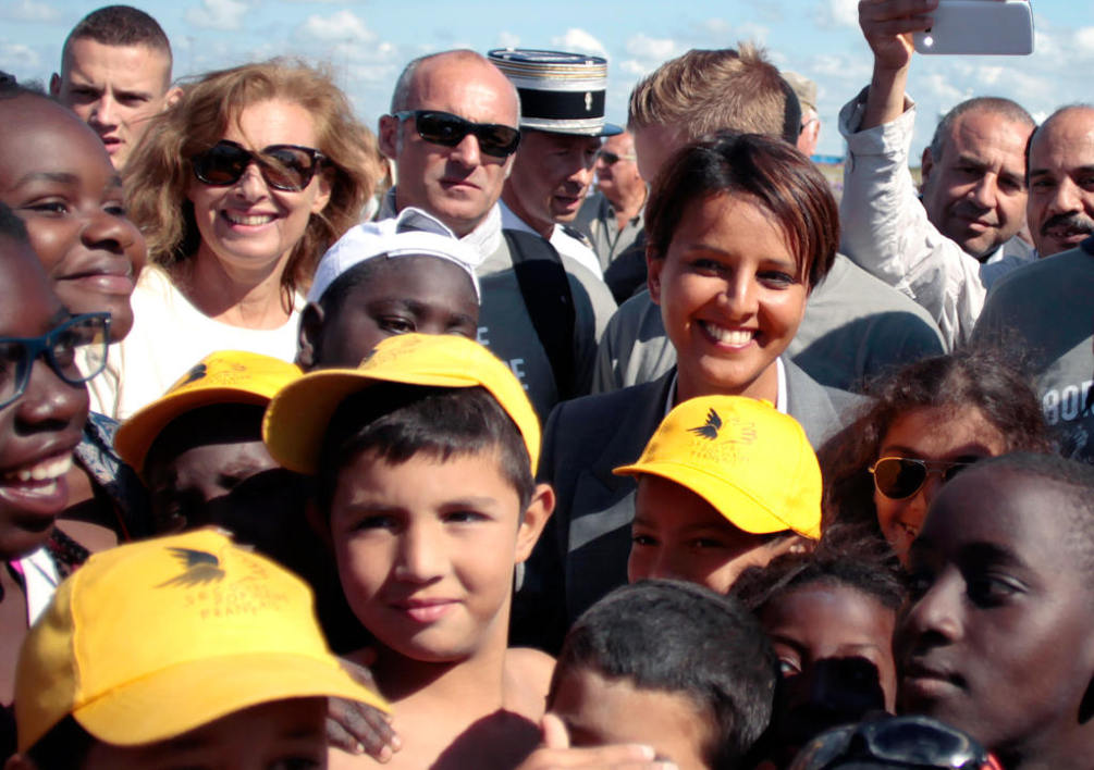 "Ouistreham : French Minister for Women's Rights and Sports Najat Vallaud-Belkacem (L) plays with French former First lady Valerie Trierweiler (R) on a beach in Ouistreham, northwestern France, on August 20, 2014 during the ""Forgotten by the Holidays"" campaign organised by the French NGO Secours Populaire for children whose families can't afford to go on holidays. AFP PHOTO/CHARLY TRIBALLEAU"