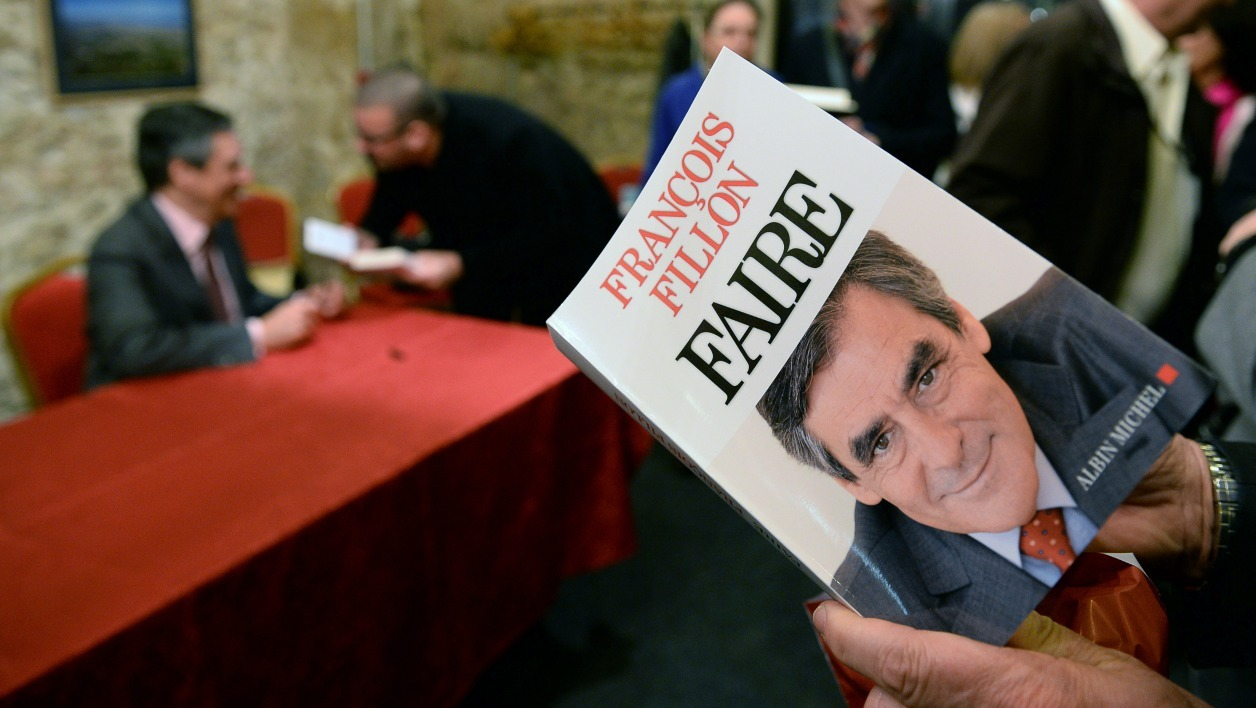 "Former French Prime Minister and right-wing Les Republicains (LR) parliament member Francois Fillon (L) signs copies of his book ""Faire"" on March 10, 2016 in Marseille.  BORIS HORVAT / AFP"