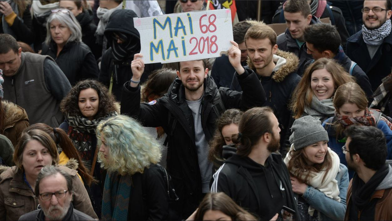A man holds a placard as he takes part in a demonstration during a nation-wide action day of French civil servants against French government's string of reforms on March 22, 2018 in Nantes, western France. Seven trade unions have called on public sector workers to strike on March 22, including school and hospital staff, civil servants and air traffic controllers.