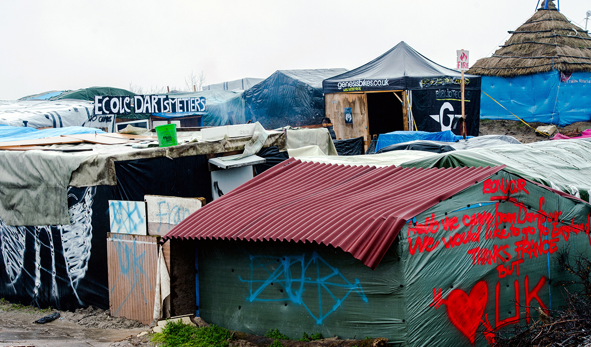 "A picture taken on February 22, 2016 in Calais shows the ""Jungle"" migrants and refugee camp. Local French government authorities said on February 12 they want to move up to 1,000 migrants living in the ""Jungle"" camp in Calais. They could be housed in a new centre of converted shipping containers which was set up this winter and can house up to 1,500 migrants, or in other centres around France. But, according to humanitarian associations the number of people living in the camp is up to 3.450 and not 1.000 as mentioned by the government."