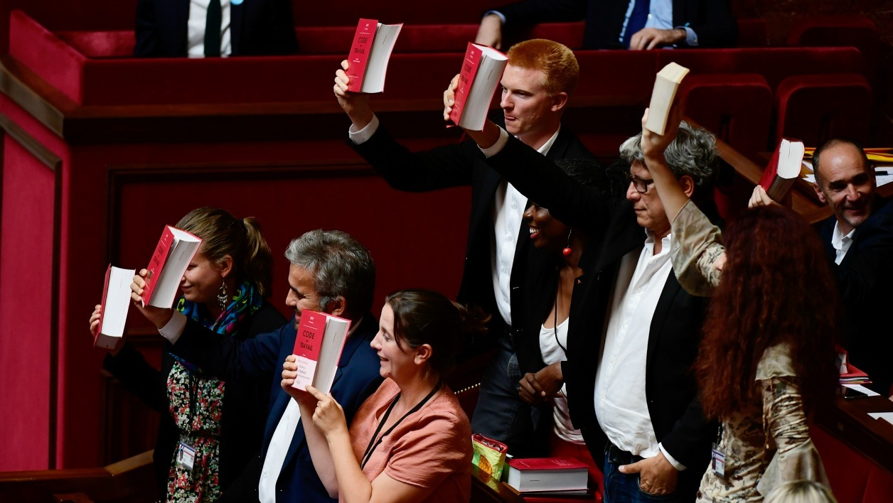 La France Insoumise (LFI) party's Members of Parliament (From L) Mathilde Panot, Alexis Corbiere, Caroline Fiat, Adrien Quatennens, Daniele Obono, Eric Coquerel, Benedicte Taurine and Loic Prud'homme hold copies of the French Labour Code after La France Insoumise (LFI) leftist party's parliamentary group president delivered a speech following the French Prime Minister's address of his general policy speech.