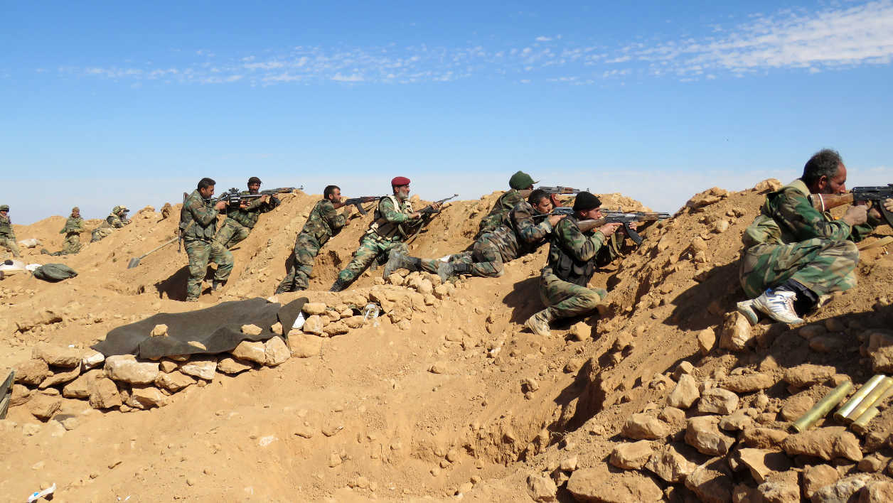 Syrian army soldiers take positions on the outskirts of Syria's Raqa region on February 19, 2016.  STRINGER / AFP Syria