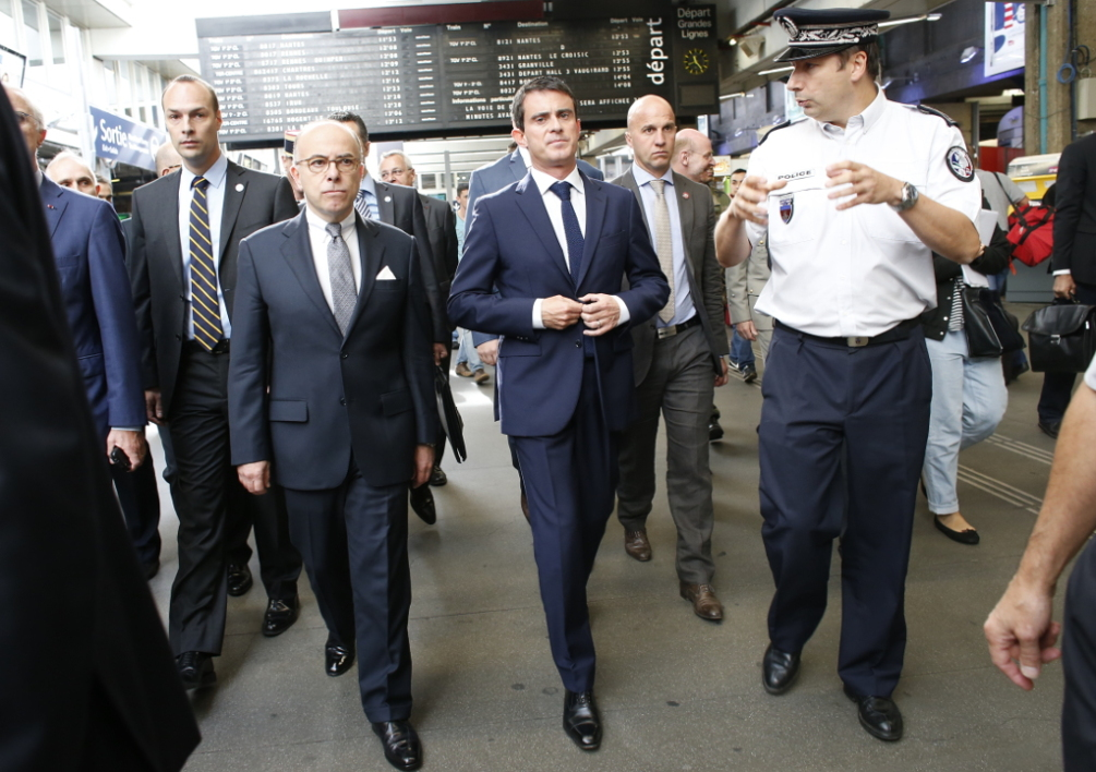 "FRANCE, Paris : French Prime Minister Manuel Valls (C) and Interior Minister Bernard Cazeneuve (C, left) listen to a police officer during a visit at the Paris Montparnasse railway station on September 28, 2014 after a reinforcement of France's national security alert system Vigipirate. Vigipirate device, designed in 1978 when Europe was wiping a wave of terrorist attacks is ""now operational and effective"" said this week French government who faces with new threats after the abduction of a French citizen in Algeria by a group linked to jihadists of the Islamic state (EI). France is on high alert after Islamic State jihadists sowing terror in Iraq and Syria issued a call for Muslims to kill citizens from countries involved in a US-led coalition fighting the extremists, ""especially the spiteful and filthy French"". AFP PHOTO THOMAS SAMSON"