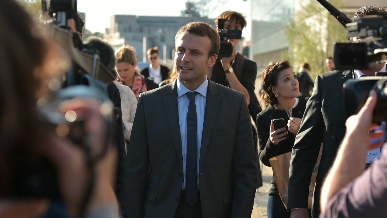 "Former French Economy Minister and founder of the political movement ""En Marche"" (On the Move) Emmanuel Macron (C) walks in streets of Strasbourg, eastern France, on October 4, 2016 as he speaks with the press, ahead of a meeting."