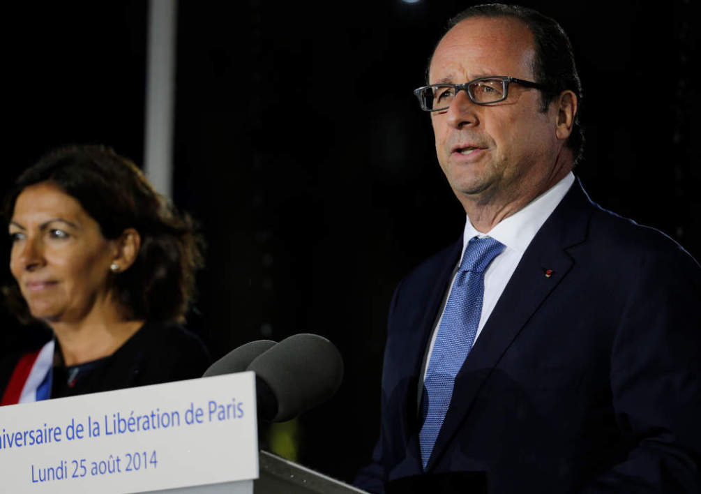 "FRANCE, Paris : French President Francois Hollande (R) gives a speech next to Paris' mayor Anne Hidalgo, on August 25, 2014, during a ceremony in front of Paris' town hall to commemorate the 70th anniversary of the liberation of Paris from Nazi occupation during World War II. Paris started on August 19, 2014 a week of celebrations for the 70th anniversary of its liberation in 1944 during the WWII, with an ultimate highlight during the evening on August 25: a light show ending with a ""popular bal"" in front the Town hall. AFP PHOTO / JOEL SAGET"