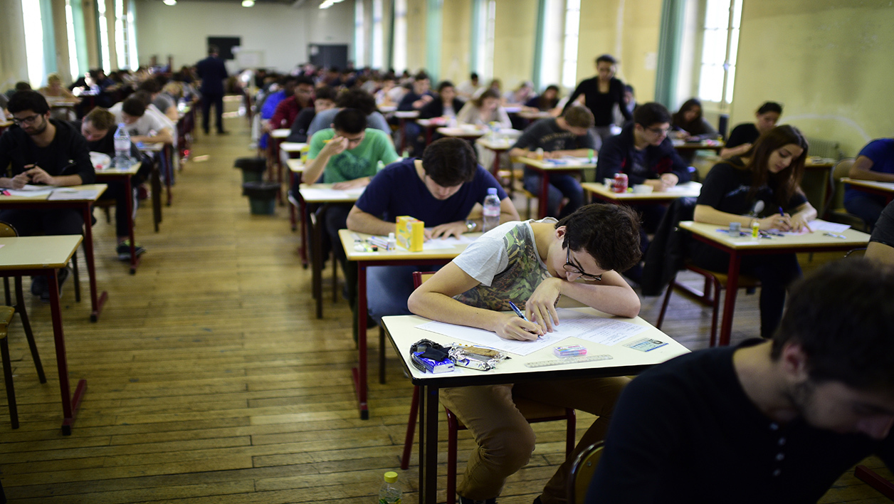 High school students sit behind desks during a philosophy exam, the first test session of the 2015 baccalaureate (high school graduation exam) on June 17, 2015 in Paris. Some 684,734 candidates registered for the exam to be held until June 24, 2015 in 4,200 examination centres. AFP PHOTO / MARTIN BUREAU