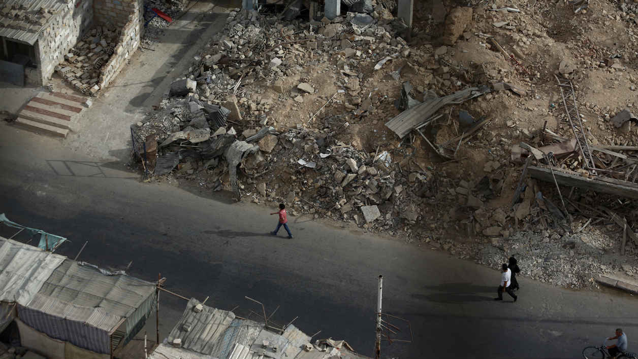 Residents walk past the rubble of destroyed buildings on September 16, 2015, in the rebel-held area of Douma, east of the Syrian capital Damascus. AFP PHOTO / ABD DOUMANY