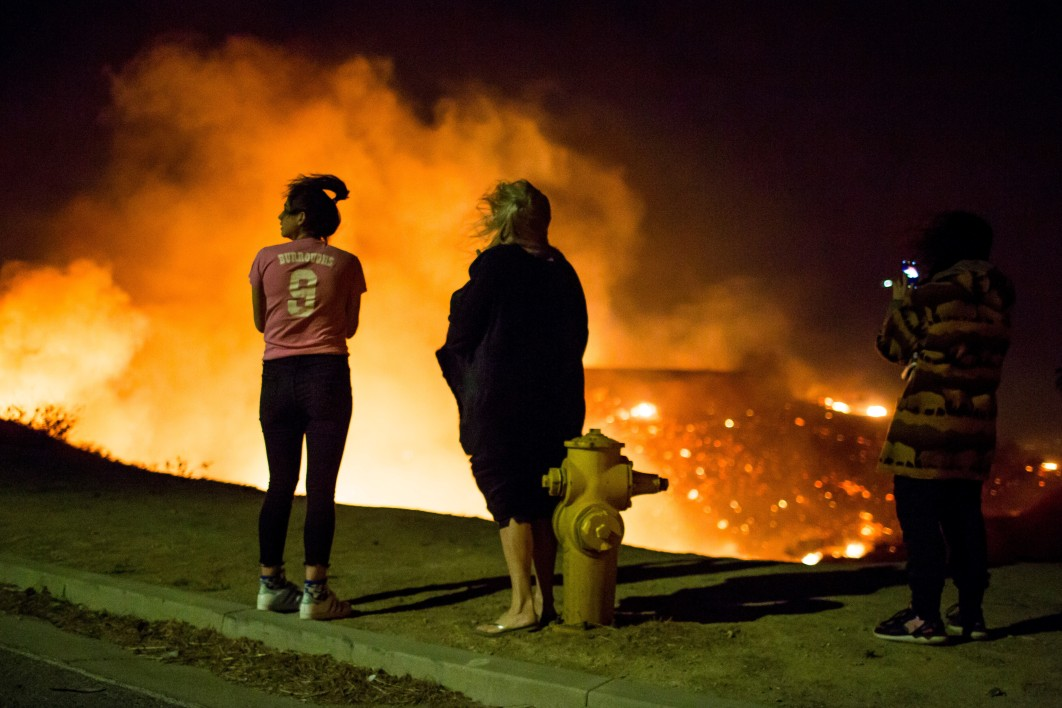 Residents watch as the Creek Fire burns along a hillside near homes in the Shadow Hills neighborhood of Los Angeles, California, on December 5, 2017. More than a thousand firefighters were struggling to contain a wind-whipped brush fire in southern California on December 5 that has left at least one person dead, sent thousands fleeing, and was choking the area with thick black smoke. Kyle Grillot / AFP