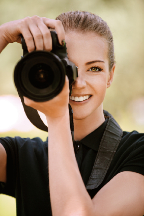 smiling young woman photographs on camera