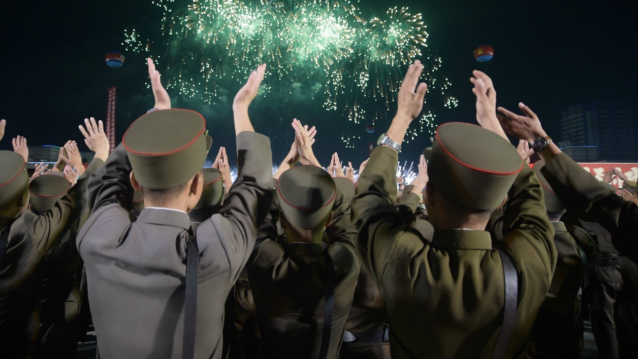 In a photo taken on September 6, 2017, Korean People's Army (KPA) soldiers cheer during a mass celebration in Pyongyang for scientists involved in carrying out North Korea's largest nuclear blast to date. Citizens of the capital lined the streets September 6 to wave pink and purple pom-poms and cheer a convoy of buses carrying the specialists into the city, and toss confetti over them as they walked into Kim Il-Sung Square.