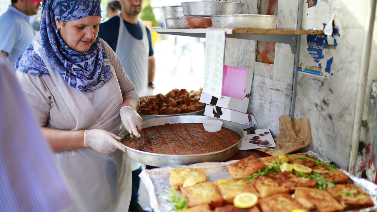 A woman prepares food for Ramadan on May 27, 2017 at a market, in the Barbes area of northern Paris. The world's nearly 1.5 billion Muslims on May 27 began Ramadan, the holy month of dawn-to-dusk fasting and prayers. BENJAMIN CREMEL / AFP