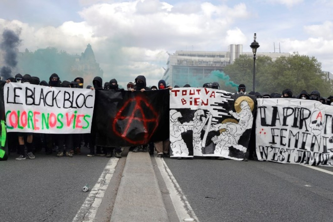"Protestors dressed in black and with the face covered hold smoke bombs and a banner reading ""The Black bloc colours our lives"" and depicting the Anarchist symbol as they take part in a march for the annual May Day workers' rally, in Paris, on May 1, 2018."