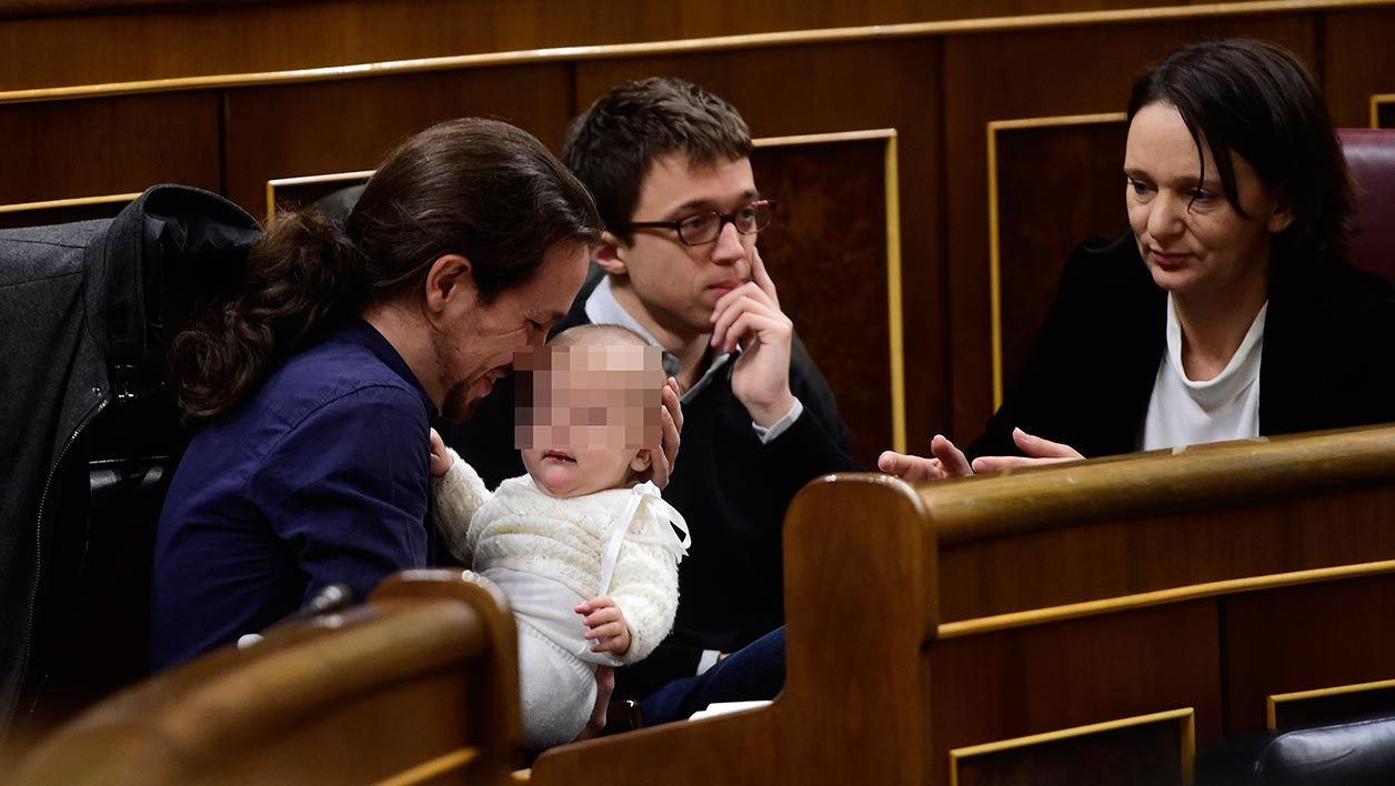 Left wing party Podemos' leader Pablo Iglesias (L) plays with the baby of Podemos' deputy Carolina Bescansa (R), past Podemos' member Inigo Errejon during the constitution of the Congress, at the Palacio de las Cortes in Madrid on January 13, 2016. Spain's parliament holds its first session today, with lawmakers from four conflicting main parties taking their seats at a time of political turmoil intensified by a resurgent secessionist threat in the Catalonia region. AFP