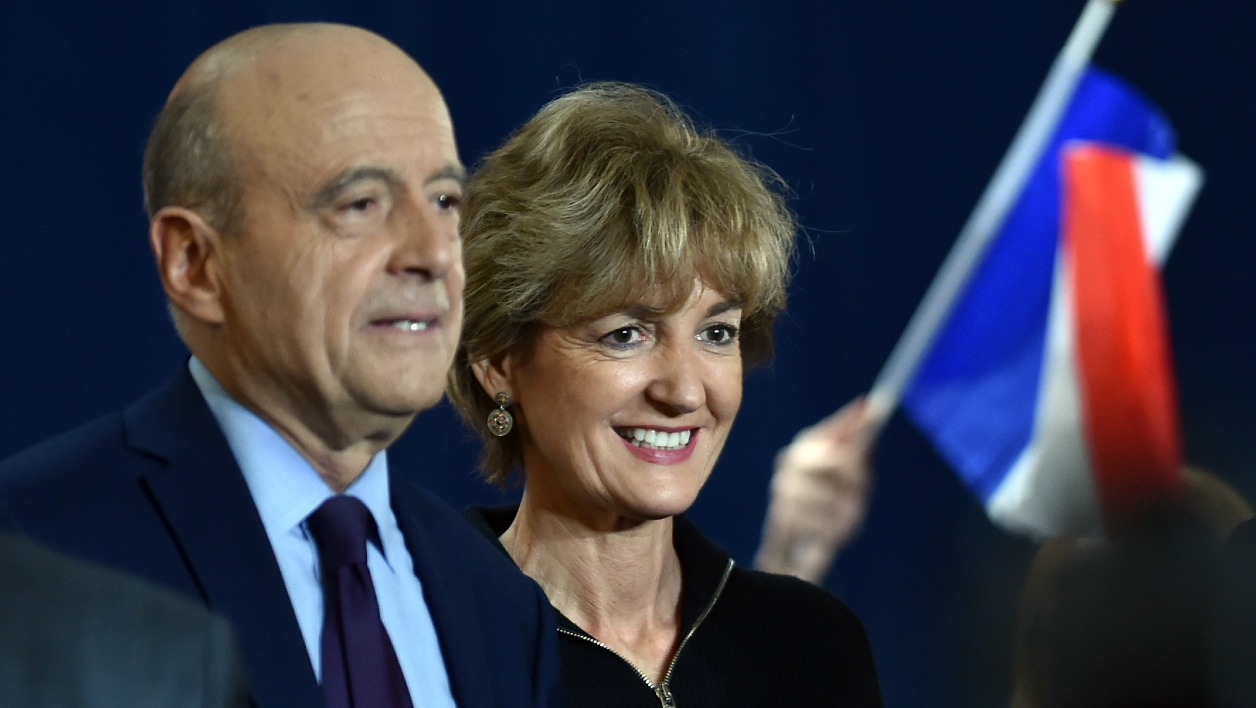 A supporter waves a French flag as Alain Juppe (L), mayor of Bordeaux and candidate for the French right-wing presidential primary, stands with his wife Isabelle Juppe during a public meeting at the Jean Mermoz hall in Toulouse, southern France, on November 22, 2016. Francois Fillon and Alain Juppe, both former prime ministers, will go head-to-head in a run-off of France's rightwing presidential primary on November 27, 2016, ahead of the presidential election of May 2017. REMY GABALDA / AFP