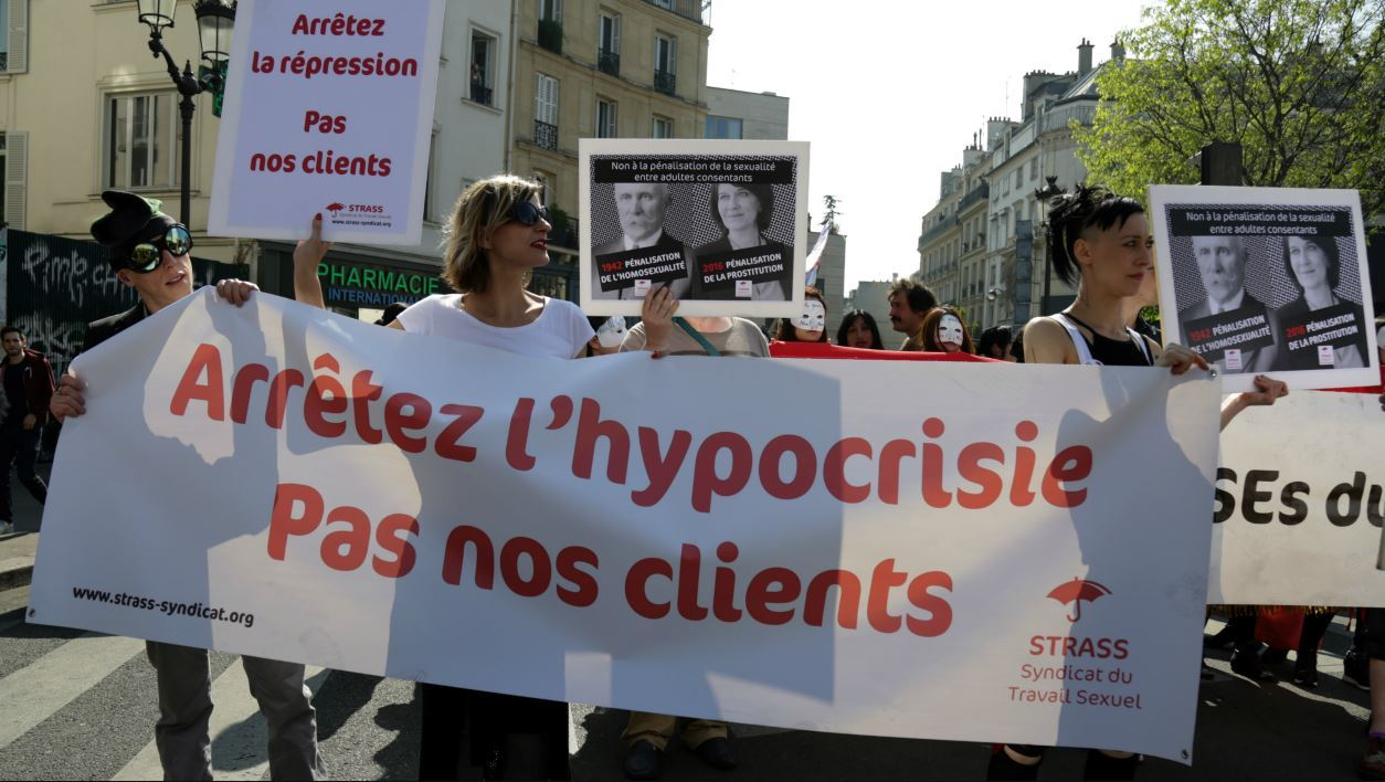Participants hold a banner reading 'Stop the hypocrisy - not our clients' during a demonstration for the rights of sex workers and prostitutes and against the criminalisation of sex work, in Paris on April 8, 2017.